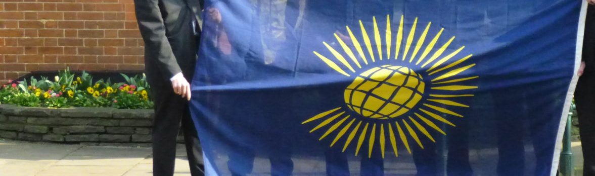 Six people holding Commonwealth flag