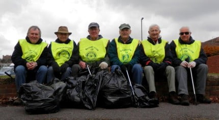 Men in yellow tabards with black sacks of rubbish.