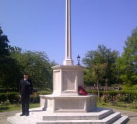 Man standing to attention on step of war memorial