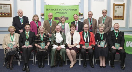 Two rows of people holding awards. Mayor and Mayoress.