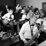 Black and white photo of band members playing musical instruments