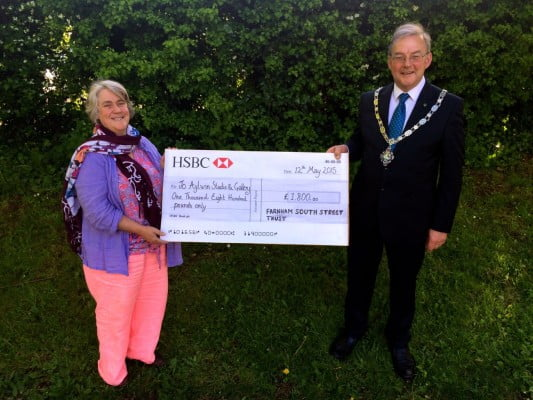 Mayor hands large cheque to lady.