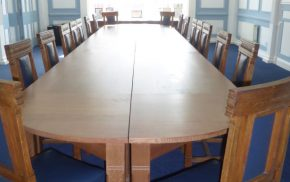 large wooden table and chairs, blue carpet.