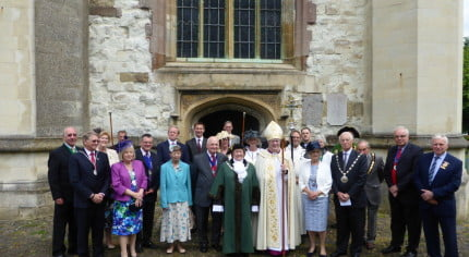 Mayors, guests and Bishop in a group outside church.
