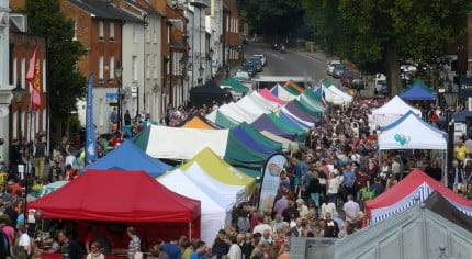 Brightly coloured marquees in street and crowds of people