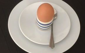 Egg in blue and white egg cup on white plate.