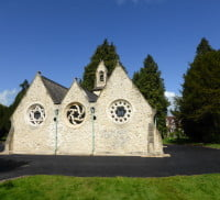 White stone chapel, tarmac driveway around, trees in the background.