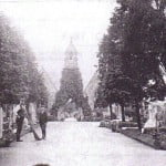 Old photo of cemetery, chapel in background, 2 males to the left.