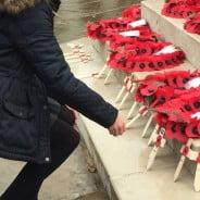 Girl lays wooden cross on war memorial.