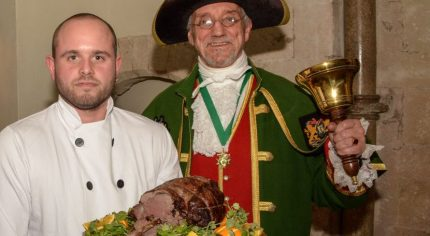Piper, chef holding venison on a platter and the Town Crier.