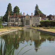 Exterior of large grand house with ornamental pond in foreground