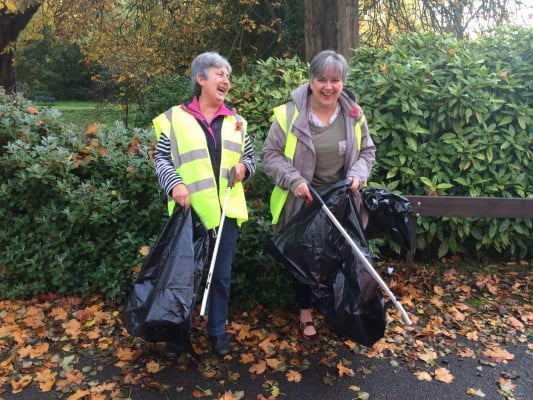 Two females in high viz jackets holding black sacks and litter pickers.