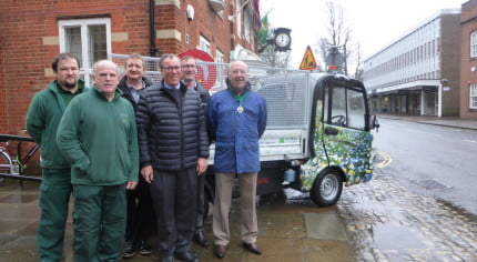 Six men in front of electric vehicle.