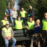 Nine males and one female sitting on a bench or standing behind wearing hi res clothing and gardening gloves
