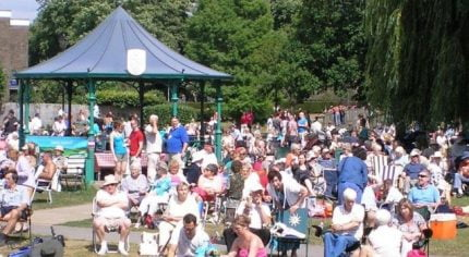 Crowd of people in park. Bandstand behind.