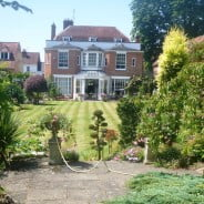 View of period house with beautiful garden in front