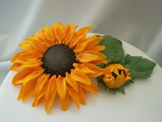 Yellow sugar paste sunflower on white cake