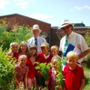 Two males with a group of school children in a garden.