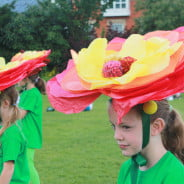 Children performers with green costumes and large flower hats .