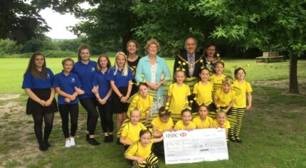 A group of adults and children with a large cheque stood in a park.