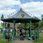 Three males playing electric guitar in a bandstand in a park.
