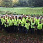 Group of people in high viz jackets with litter pickers and black sacks.