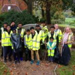 Group of young people with litter pickers and black sacks.