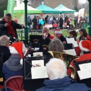 Orchestra playing in a bandstand and wearing Christmas hats.