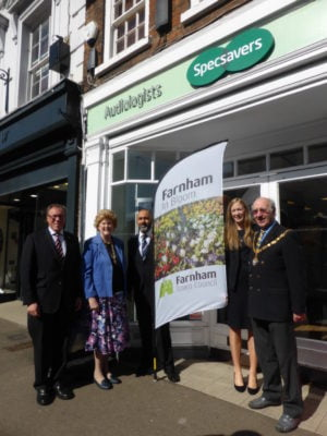 Five people standing with Farnham in Bloom sail flag outside Specsavers shop.