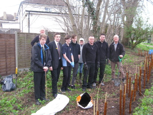 Four boys in school uniform with five adults. Standing in front of newly planted hedge.