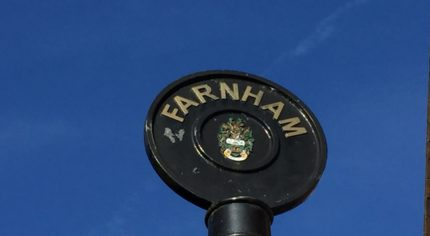 Rounded top of black iron sign post with Farnham painted in gold lettering.