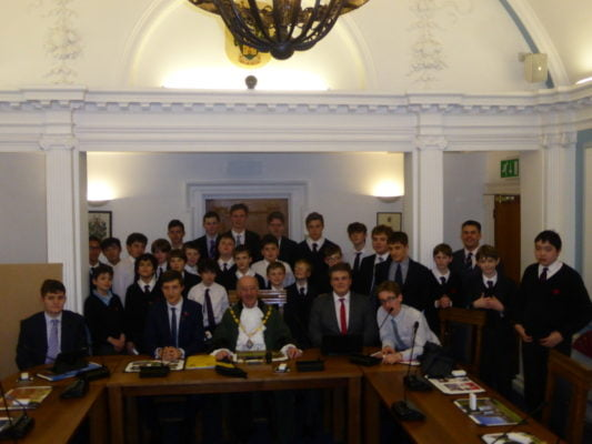 Group of schoolboys in Farnham council chamber with the Mayor of Farnham.