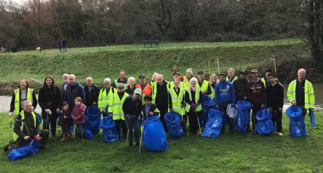 Group of people wearing high viz jackets and standing on grassy area holding blue sacks and litter pickers.
