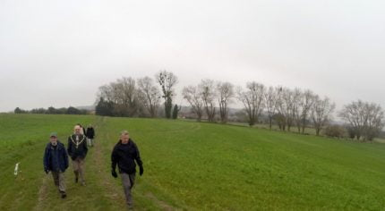 People in field with trees in background. Winter scene