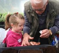 Male and child planting seeds at gardening workshop.