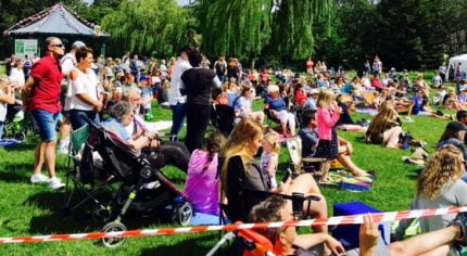 Large crowd of people sit and stand on grass to watch dance festival. Blue sky.