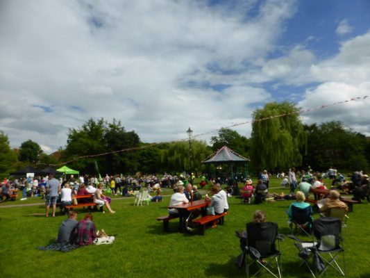 People sitting on grass and at picnic tables. Blue sky, bandstand in background.
