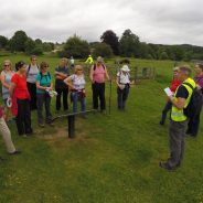 Group of walkers standing in field listening to walk guide.