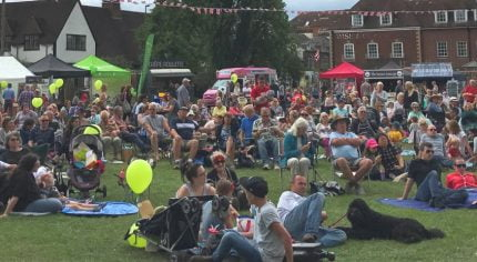 Lots of people siting on grass enjoying a music festival and picnic