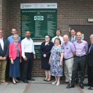 Group of people standing in front of green board showing the names of sponsors of Farnham in Bloom.