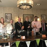 Mayor and group of people holding gin glasses.