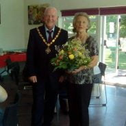 Mayor presenting female with a bouquet of flowers.