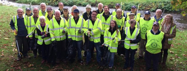 Group of litter pickers in high viz jackets and holding bags and litter picks