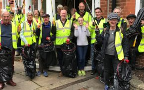 Group of people in high visibility jackets holding litter pickers and black sacks