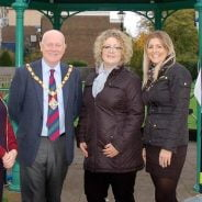 Mayor and three females in front of bandstand decorated with Christmas decorations.