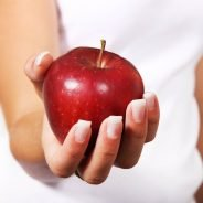 Female hand holding a shiny red apple.