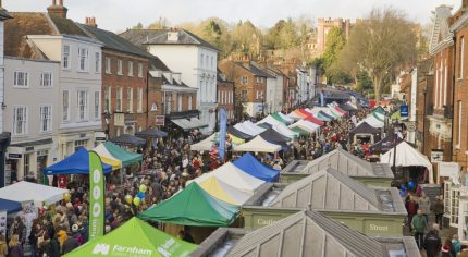 Aerial view of a crowded market with people and marquees.