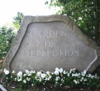 Large stone engraved with the words Garden of Reflection. White flowers at base of stone.