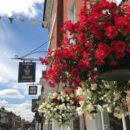 Hanging baskets with red and white flowers in West Street, Farnham