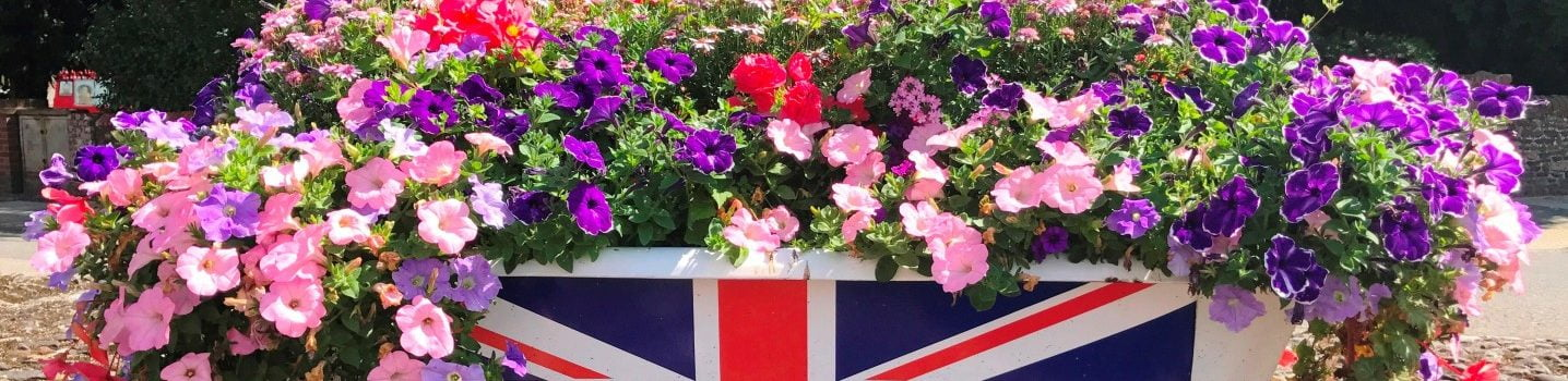 Bath tub filled with flowers and a union flag on side of bath.